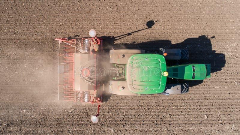 Bonde med traktoren med seederen som sår kärna ur skördar på det jordbruks- fältet Top beskådar arkivfoto