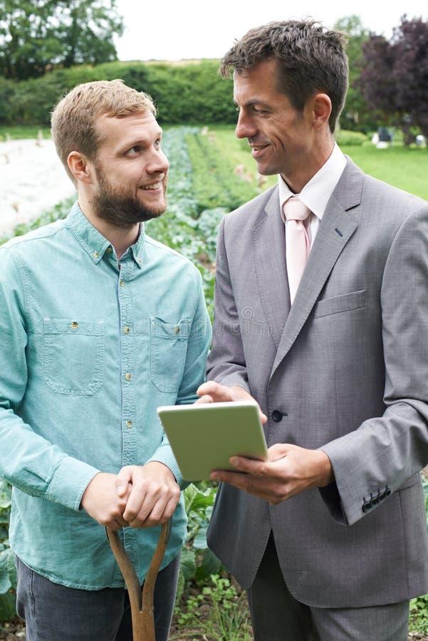 Bonde Meeting With Businessman i fält royaltyfri bild