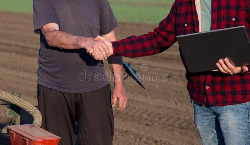 Bonde och tekniker som skakar händer i fält arkivfoto