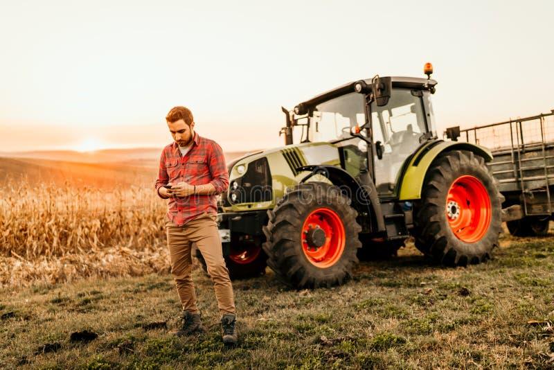 bonde som arbetar på fält genom att använda smartphonen i modernt jordbruk - traktorbakgrund arkivbild