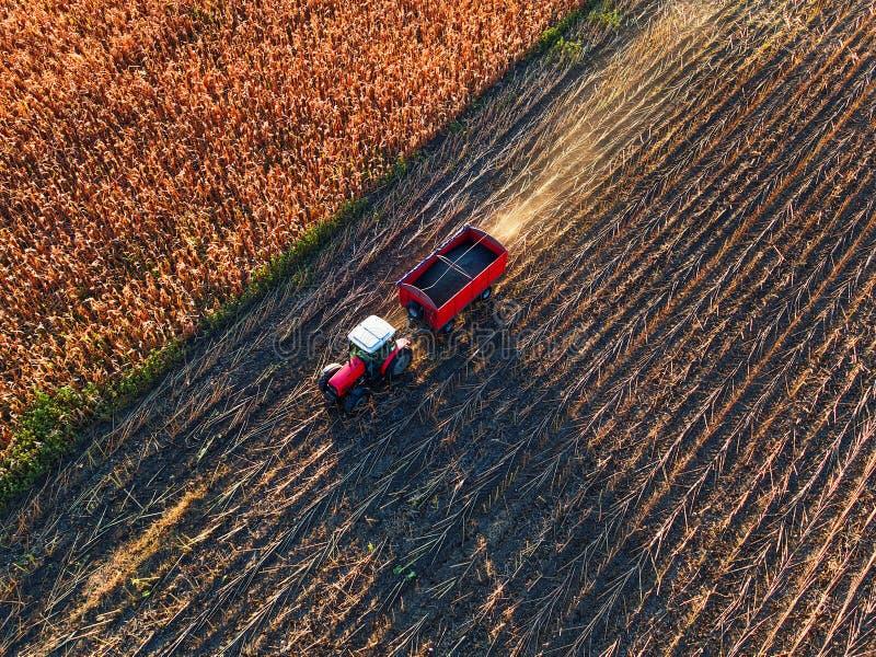 Bonde som mycket kör den jordbruks- traktoren och släpet av korn royaltyfria bilder