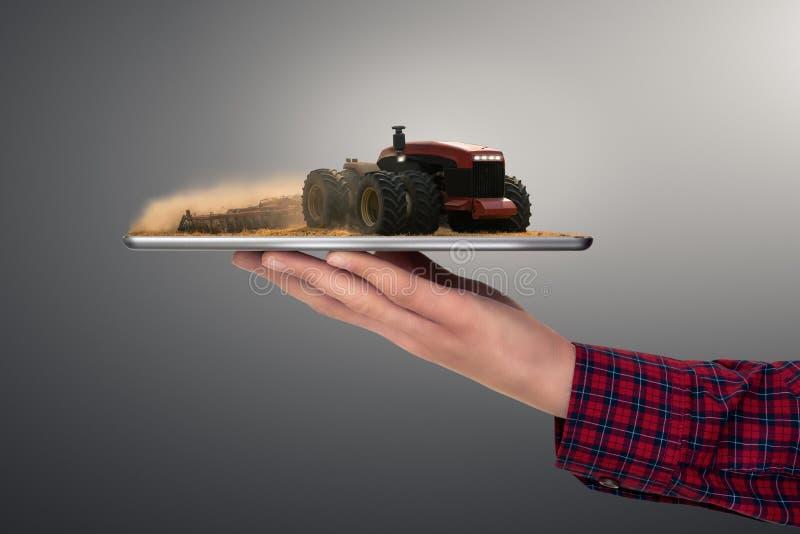 Bonde som rymmer en minnestavla med den autonoma traktoren royaltyfria bilder