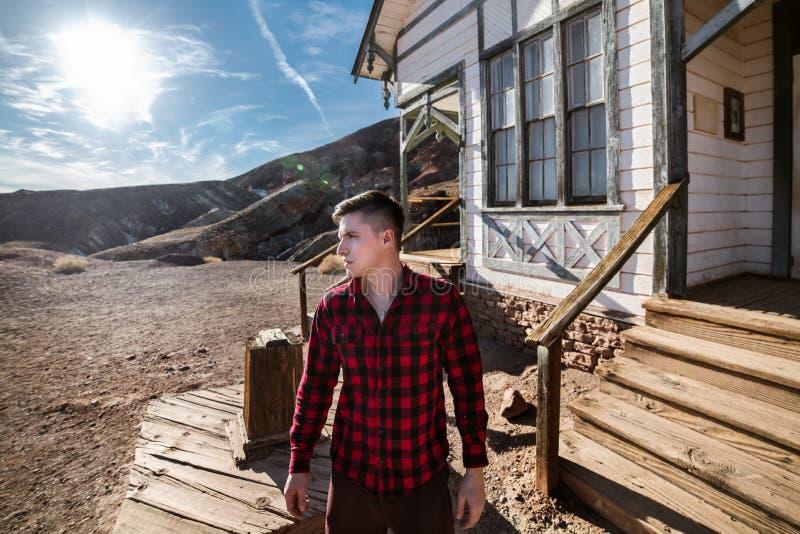 Bondebygdman som framme står av hans hus i ökenbergen som bär den röda rutiga skjortan fotografering för bildbyråer