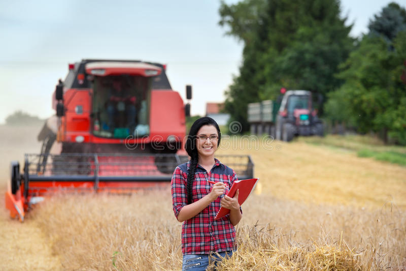 Bondeflicka på fält med skördetröskan arkivfoto