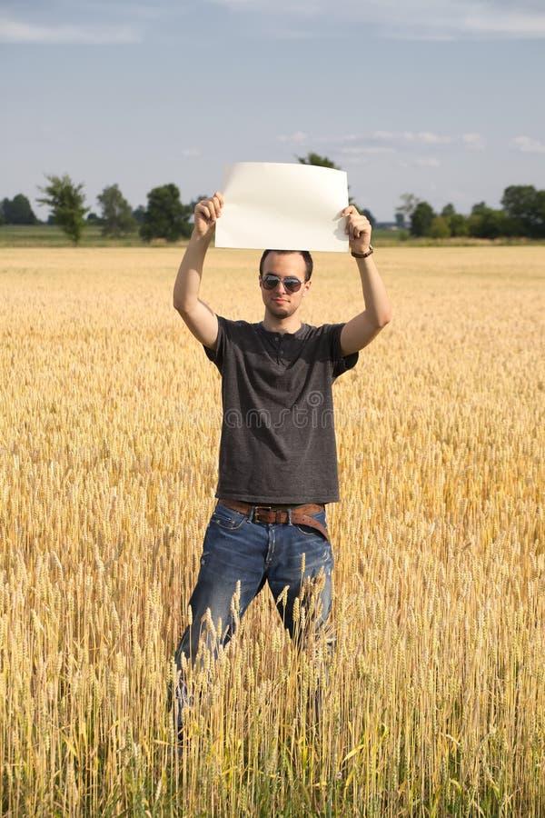 Bondegrabb i wheatfielden som rymmer det blanka tecknet arkivfoton