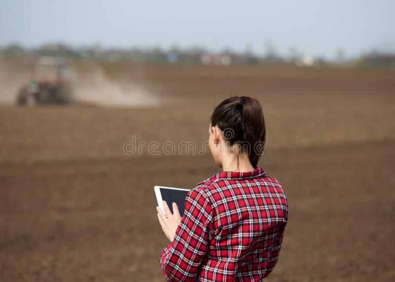 Bondekvinna med minnestavlan och traktoren i f?lt royaltyfria foton