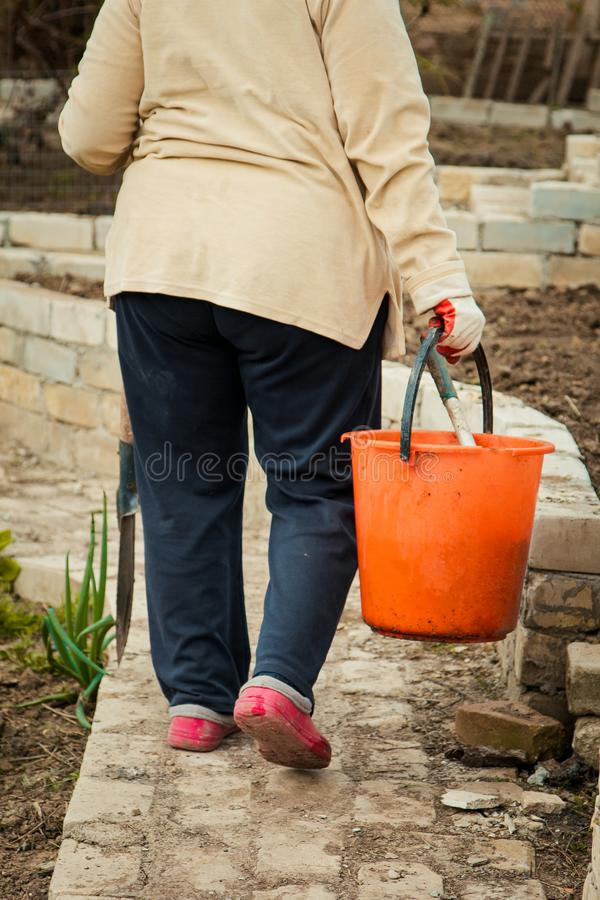 Bondekvinna som bär gå för hink som är utomhus- arkivbild