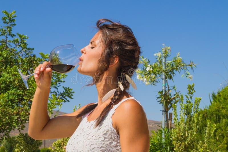 Bonden för den unga kvinnan smakar ett exponeringsglas av rött vin arkivfoto
