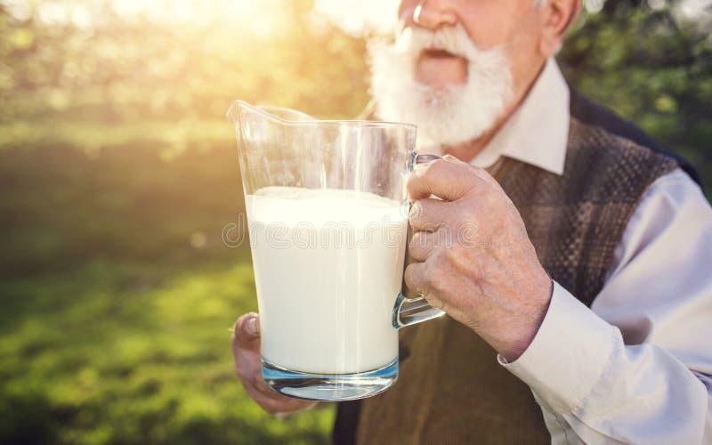 Bonden med mjölkar tillbringaren arkivfoto