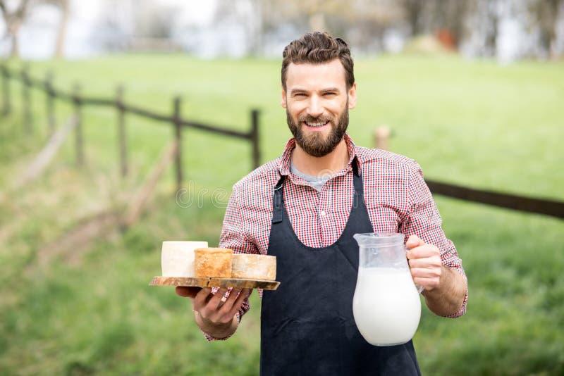 Bonden med ost och mjölkar arkivbilder