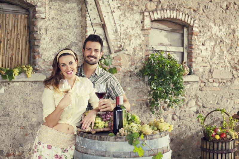 Bondepar som dricker vin i en lantgård royaltyfria bilder