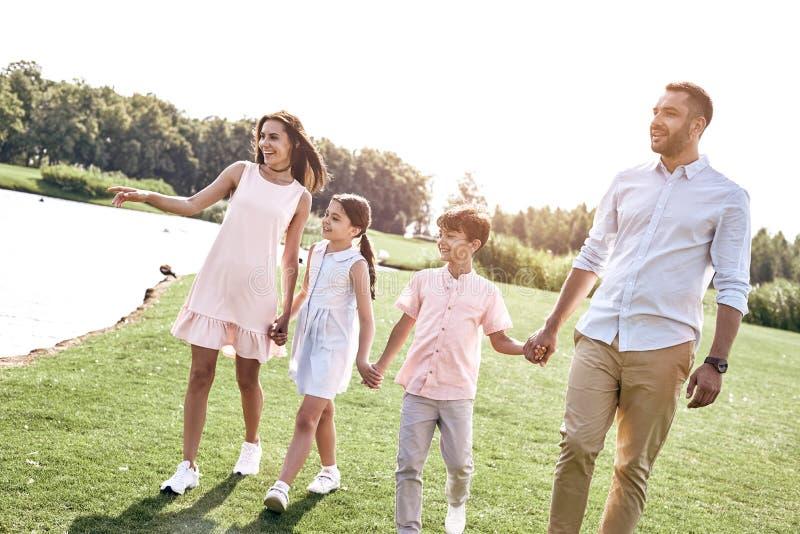 bonding Famiglia di quattro che cammina su un campo erboso vicino alla tenuta del lago immagini stock libere da diritti