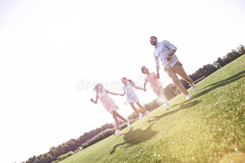 bonding Famiglia di quattro che mantene sul cheerfu di risata del campo erboso immagine stock libera da diritti