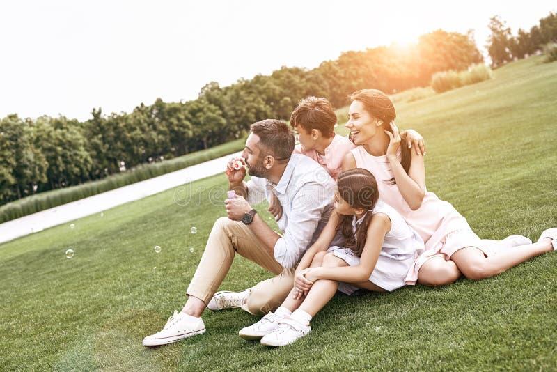 bonding Famiglia di quattro che si siede su una bolla di salto del campo erboso fotografia stock