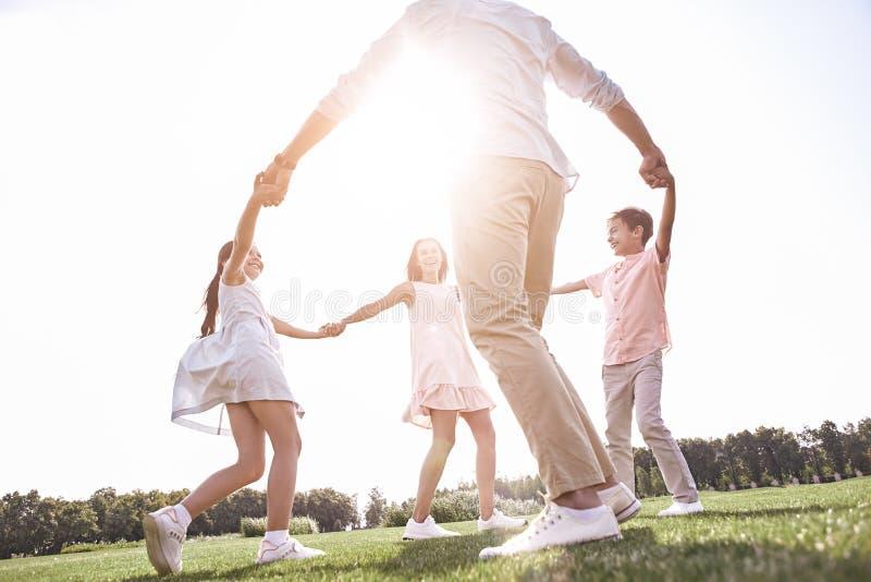 bonding Famiglia di quattro che si tiene per mano dancing nel cerchio su un gra immagini stock libere da diritti