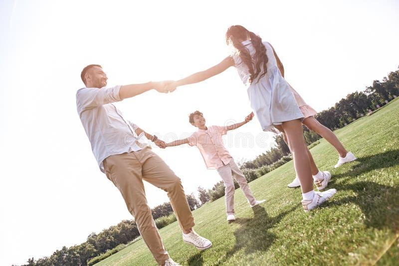 bonding Famiglia di quattro che si tiene per mano dancing nel cerchio su un gra fotografia stock