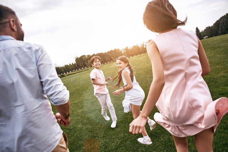 bonding familie van vier die op clos van een grasrijk gebieds achtermening lopen royalty-vrije stock afbeelding