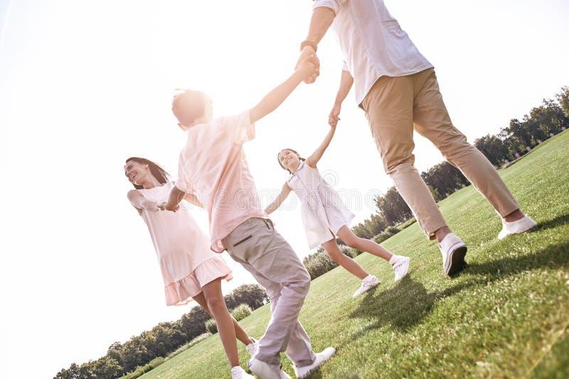 bonding Familie van vier handen houden die dansend in cirkel op een gra royalty-vrije stock fotografie