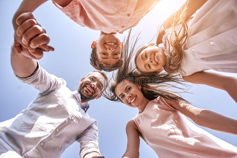 Bonding. Family of four standing in circle looking down the came. Ra smiling cheerful bottom view close-up stock photography