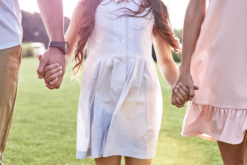 Bonding. Family of three holding hands walking on grassy field d royalty free stock photography