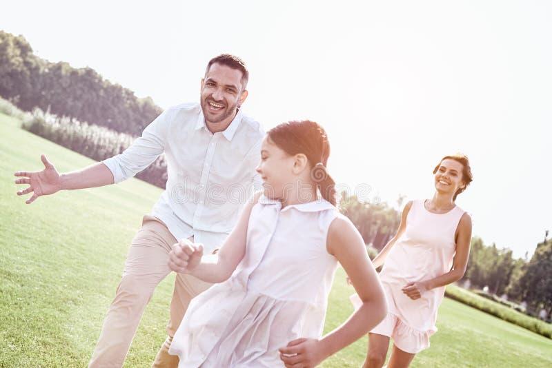 bonding Rodzina biega na trawiastym polu bawić się bawić się trzy obrazy stock