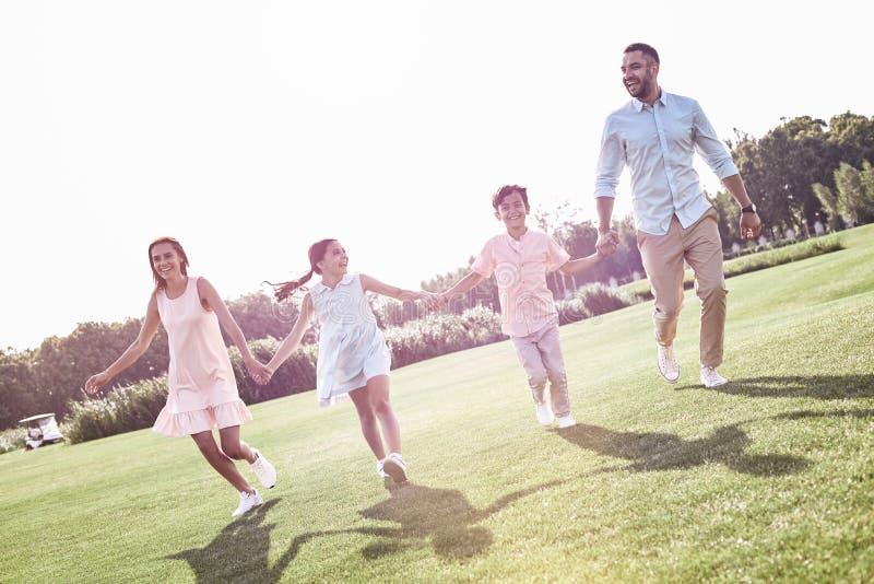 bonding Rodzina składająca się z czterech osób biega na trawiasty śródpolny ono uśmiecha się rozochocony fotografia stock
