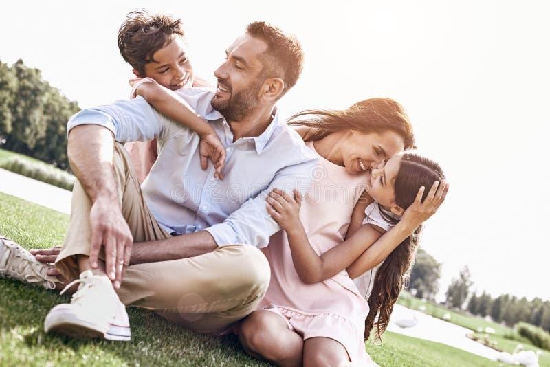 bonding Rodzina składająca się z czterech osób siedzi na trawiastym śródpolnym przytulenia laughi zdjęcie royalty free