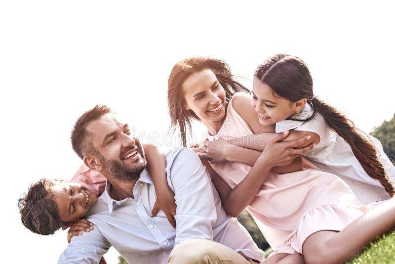 bonding Rodzina składająca się z czterech osób siedzi na trawiastym śródpolnym przytulenia smilin zdjęcia royalty free