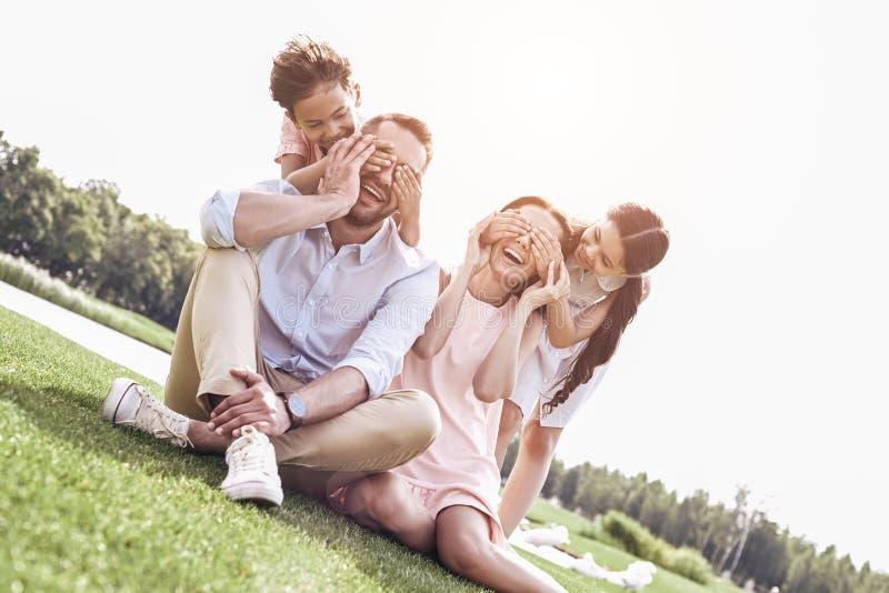 bonding Rodzinny og cztery siedzi na trawiastym polu żartuje robić su zdjęcie stock