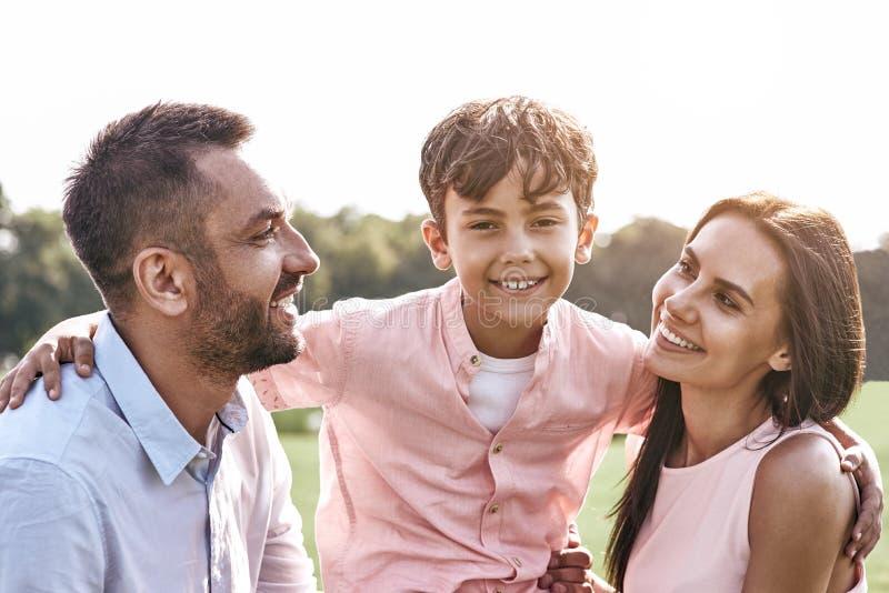 bonding Una famiglia di tre che cammina sul figlio erboso del campo che abbraccia parità fotografie stock