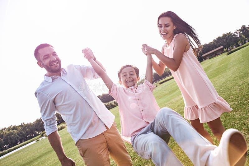 bonding Una famiglia di tre che cammina sul figlio erboso della tenuta del campo su immagine stock libera da diritti