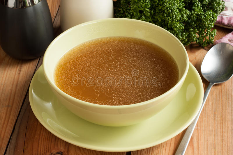 Bone broth made from beef, served in a green soup bowl stock images