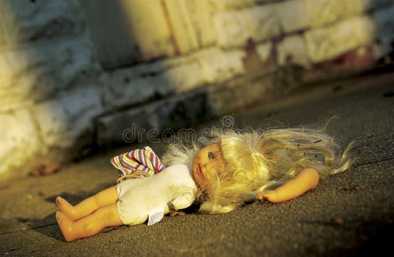 Boneca abusada que encontra-se na terra foto de stock royalty free