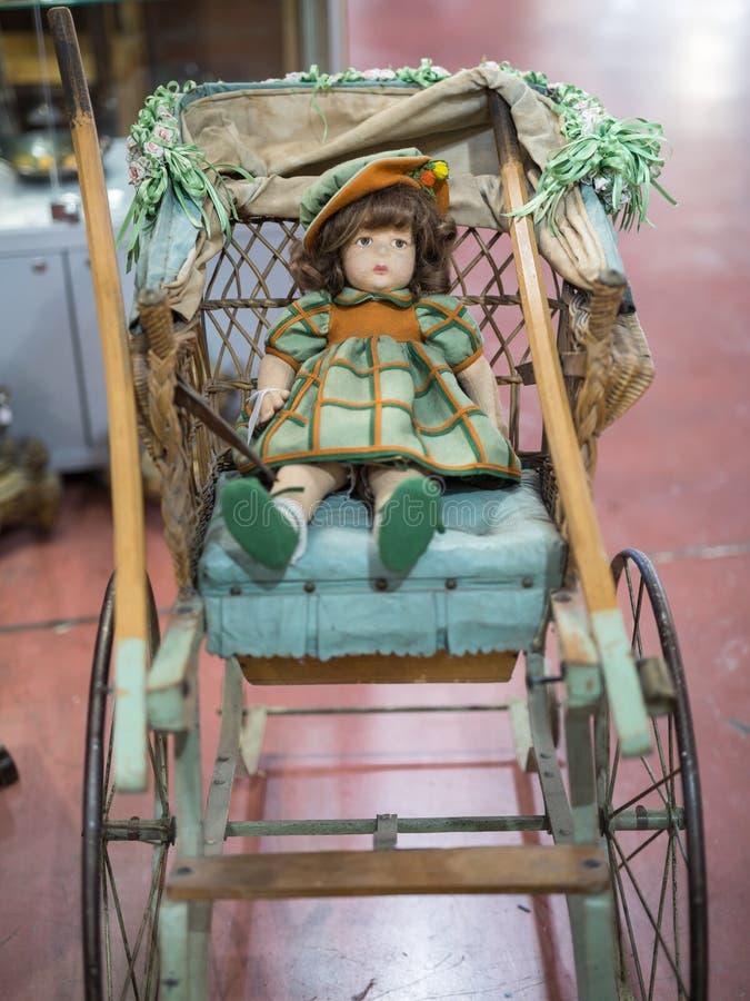 Boneca antiga com o vestido verde e alaranjado que descansa em um carrinho de criança de madeira e de vime foto de stock