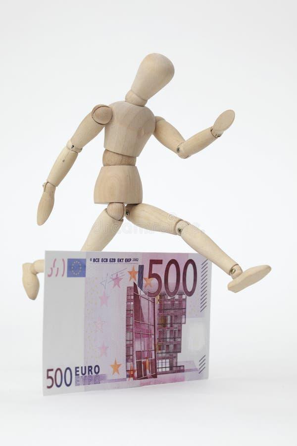 Boneca articulada que salta sobre um 500-Euro-Banknote fotos de stock royalty free