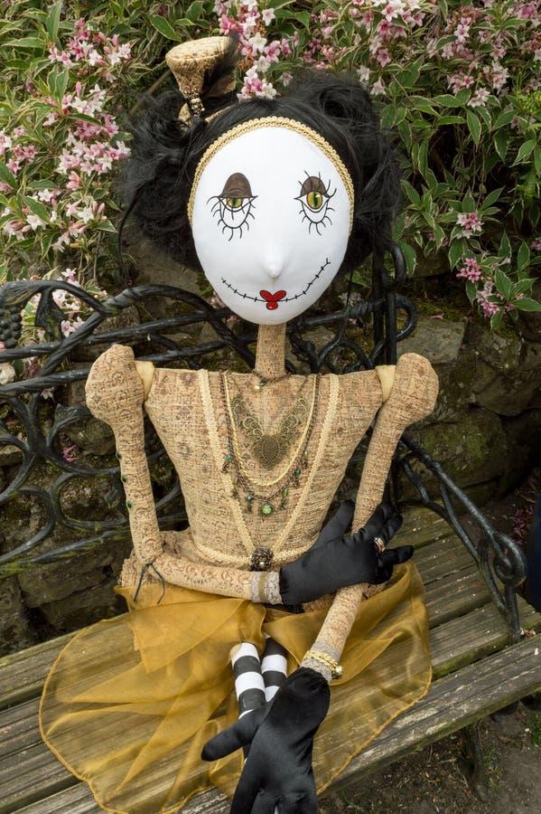 Boneca assustador do steampunk que senta-se no banco do jardim Fim acima imagem de stock