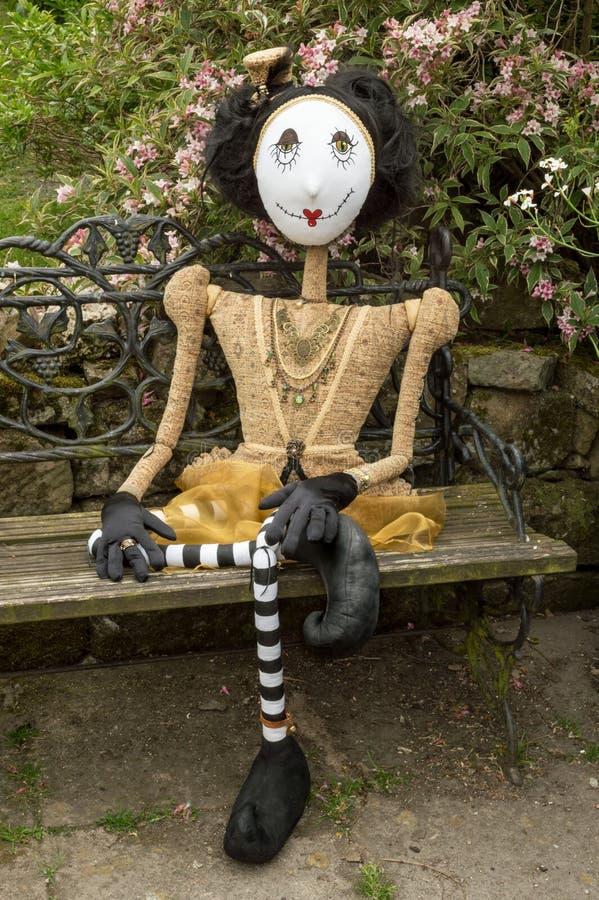 Boneca assustador do steampunk que senta-se no banco do jardim Pé cruzado foto de stock royalty free