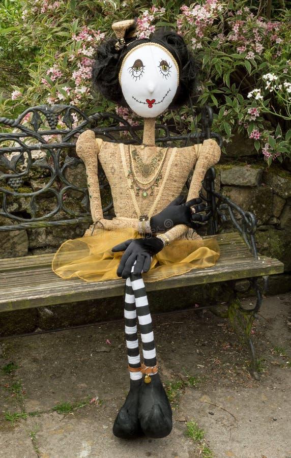 Boneca assustador do steampunk que senta-se no banco do jardim Pés cruzados imagem de stock royalty free