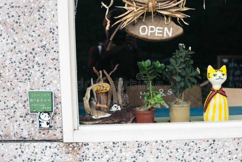 A boneca bonito do gato e abre o sinal de madeira largo através do vidro da janela de loja imagem de stock