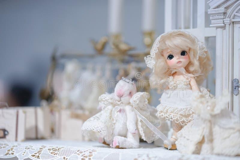 Boneca bonito na exposição Menina inocente de Kawaii com cabelo louro em um vestido branco do laço fotografia de stock royalty free