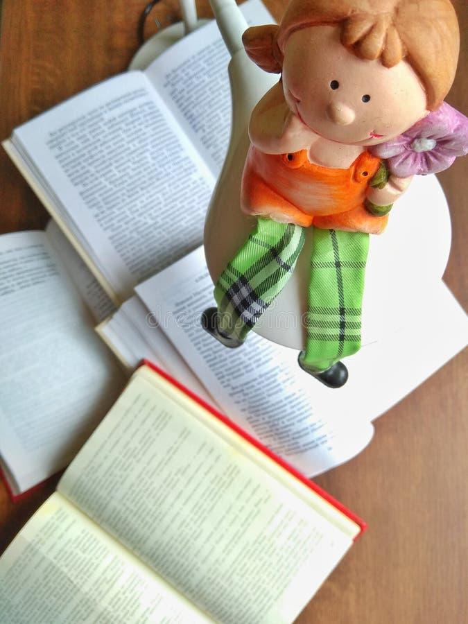 A boneca da argila senta-se na lâmpada Muitos livros abertos em uma tabela de madeira foto de stock