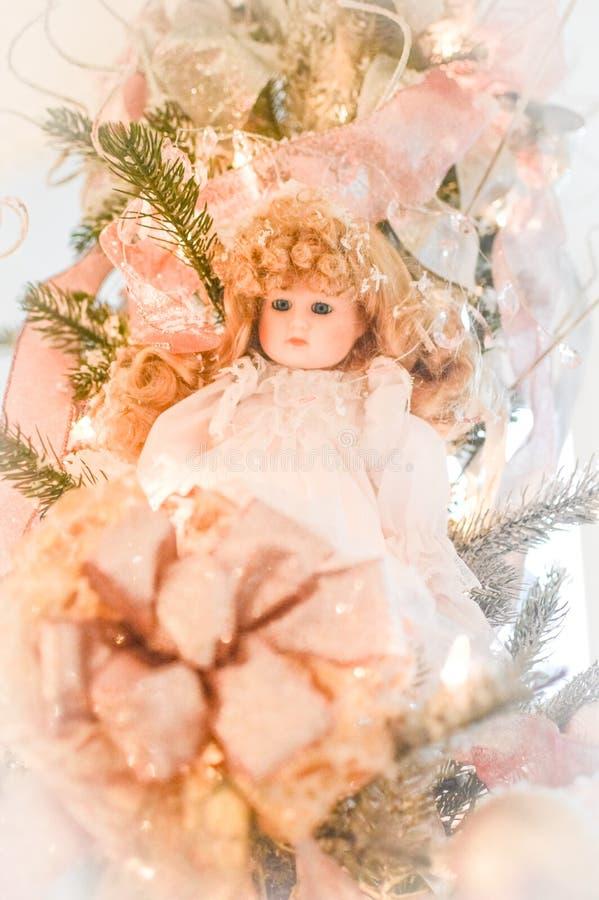 Boneca da porcelana com o vestido cor-de-rosa na árvore de Natal imagens de stock