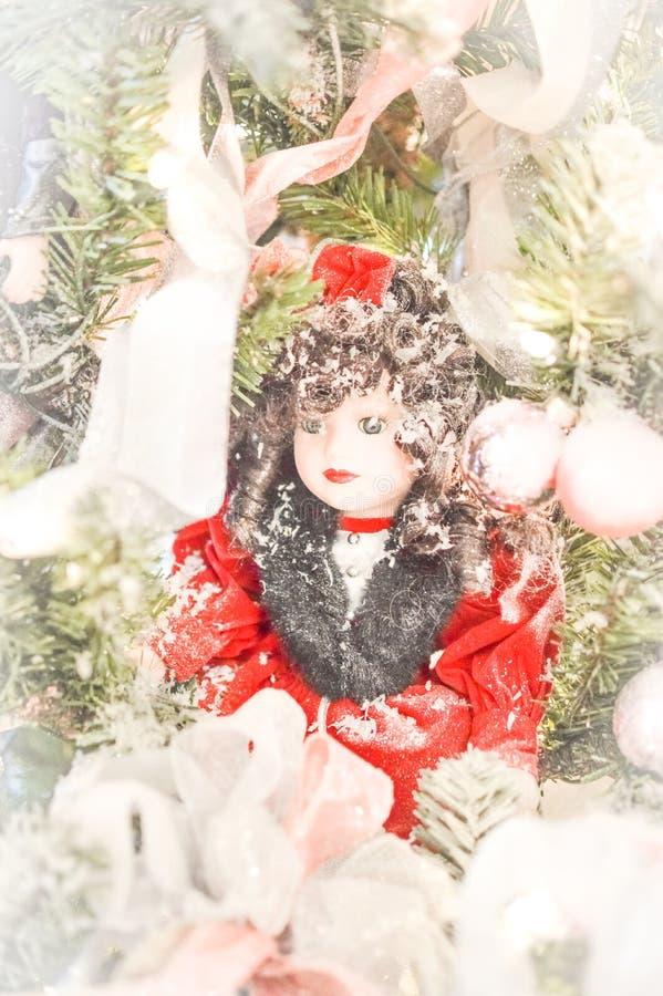 Boneca da porcelana com o vestido vermelho na árvore de Natal foto de stock royalty free