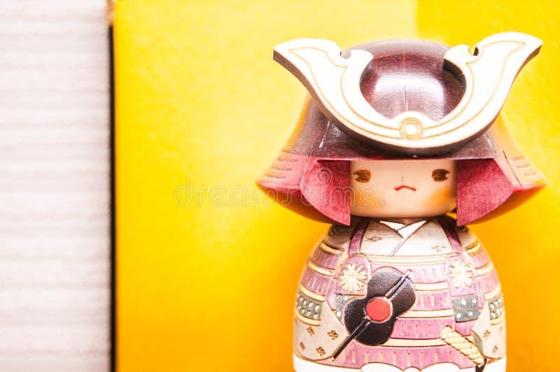 Boneca de madeira japonesa, Kokeshi, samurai Kokeshi no fundo amarelo imagem de stock