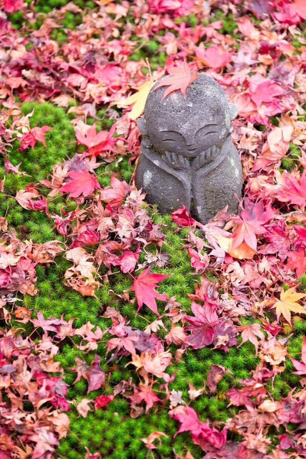 Boneca de pedra bonito e folhas de bordo da escultura no templo de Enkoji imagens de stock royalty free