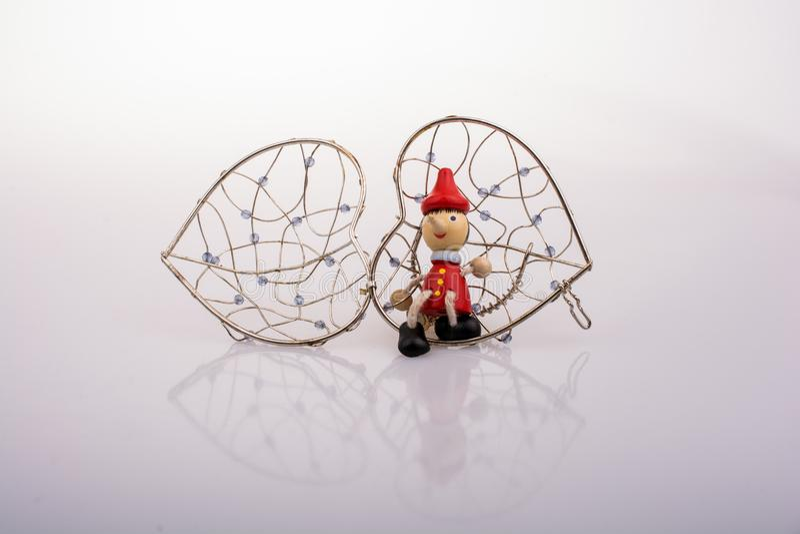 A boneca de Pinocchio que senta-se em um coração deu forma à gaiola imagens de stock royalty free