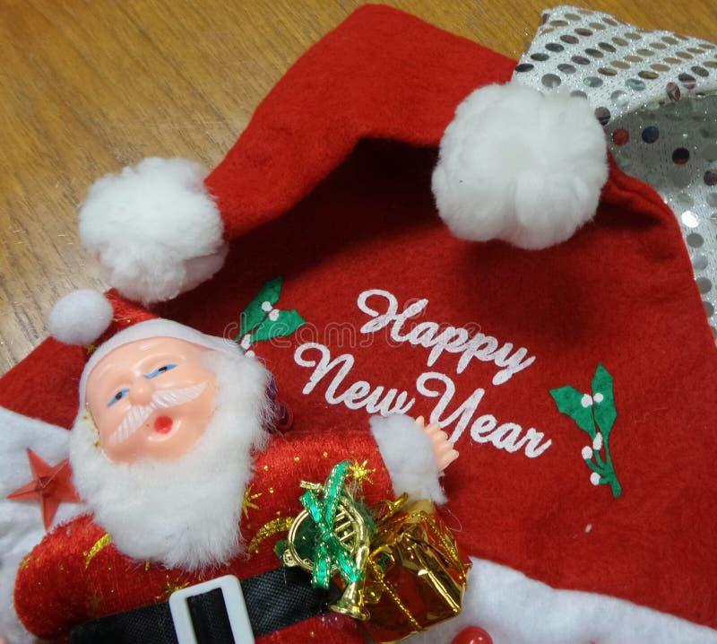 Boneca de Santa Claus e mensagem branca do ano novo feliz no chapéu vermelho de Santa foto de stock royalty free