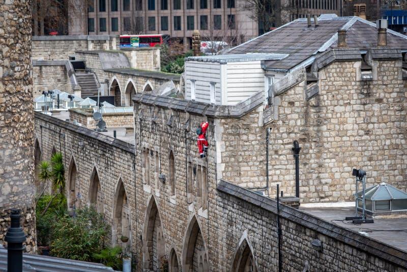 Boneca de Santa Claus que escala uma escada na parede de tijolos velha fotografia de stock