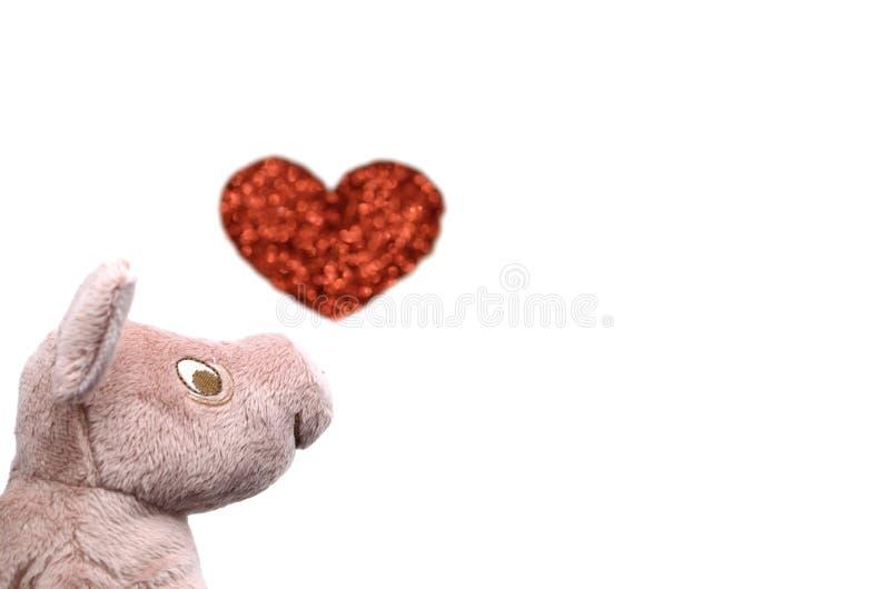 A boneca de sorriso do porco com a foto borrada da forma do amor imagens de stock royalty free
