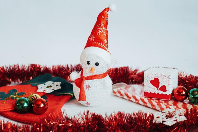 Boneca do boneco de neve e decorações claras do Natal em um b de madeira branco imagens de stock